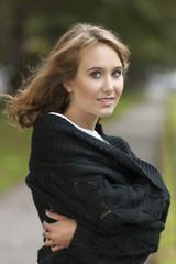 Hübsche junge Frau friert draußen im Herbst