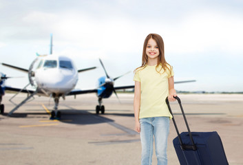 smiling girl with travel bag in airport