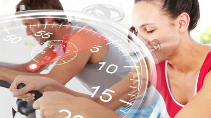 Stopwatch graphic over couple using exercise bikes