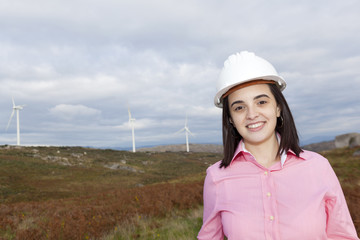 Portrait of a confident female engineer standing at wind turbine
