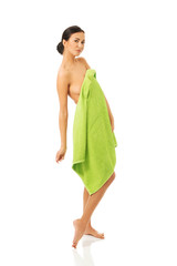 Full length woman standing wrapped in towel