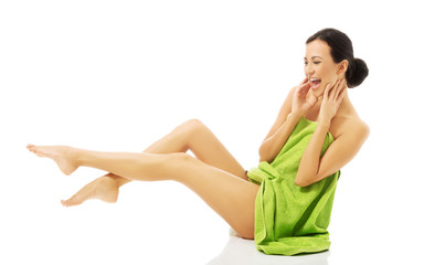 Side view woman wrapped in towel with legs up
