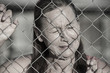 Stressed Crying woman at prison fence