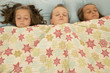 boy and two girls asleep under a blanket