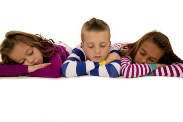Three children laying down wearing winter pajamas asleep