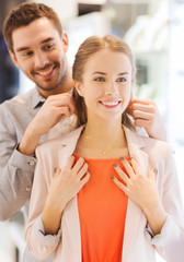 couple trying golden pendant on at jewelry store