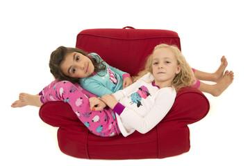 Two cute girls wearing winter pajamas relaxing