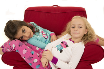 Girls wearing winter pajamas sitting in a red chair