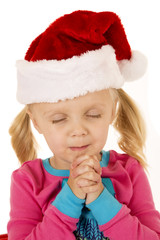 Cute young girl praying wearing a santa hat