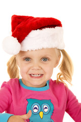 excited young girl smilining wearing a santa hat