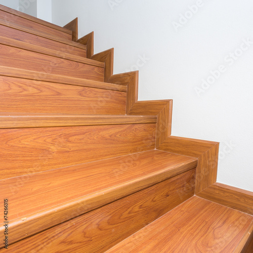 wooden staircase made from laminate wood in white modern house - 74266315