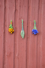 medical flowers and wheat bunch on red house wall