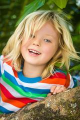 Happy, healthy child climbing tree at the beach