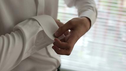 The man in the white shirt dress cufflinks.
