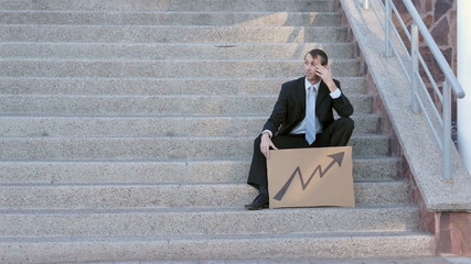 Businessman Sits On Steps Economic Arrow