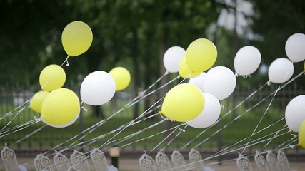 White and yellow balloons tied to a chair developed in the wind