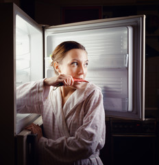 Young woman looking for some snack in fridge late at night