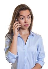 Frau mit langen braunen Haaren bedrückt am Handy