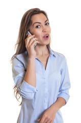 Frau mit langen braunen Haaren telefoniert