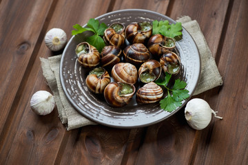 Bourgogne snails with garlic butter, rustic brown wooden surface