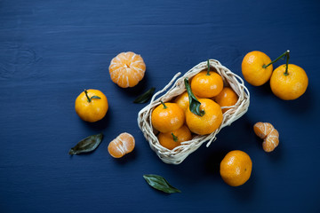 Still life with ripe tangerines on a dark blue wooden surface