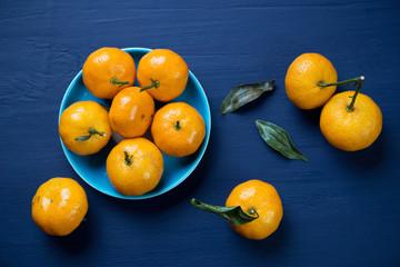 Mandarins over dark blue wooden background, above view
