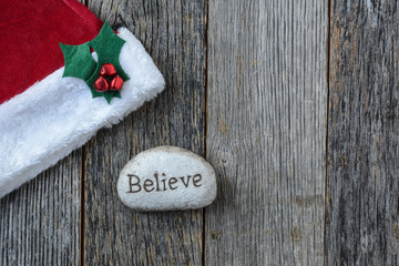 Santa Hat with the text Believe on a Stone Rock on Wood Backgrou