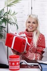 Lächelnde Büroangestellte mit Weihnachtsgeschenk