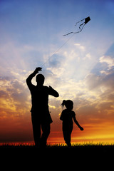 girl and father with kite at sunset