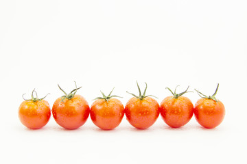 Fresh drops tomatoes in straight line