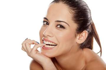 Portrait of beautiful young happy woman nibbling on her finger