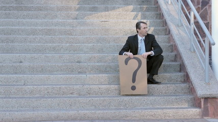 Businessman on Steps with Question Mark Sign