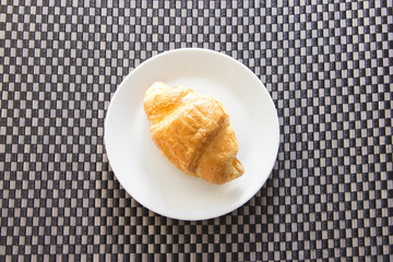 Croissant on plate contrast with mat pattern