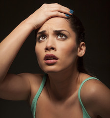 portrait of a young frustrated beautiful woman touching her head