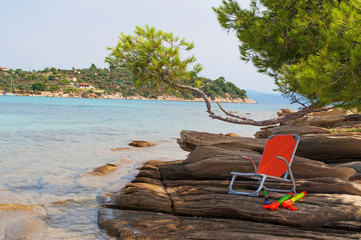 Chair in the shade on the beach rocks