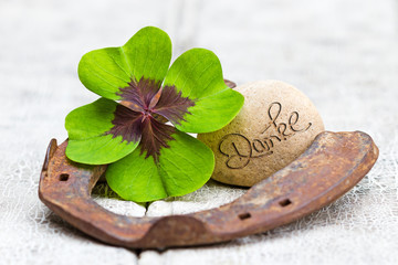 Glücksbringer und Stein auf Holz, Danke