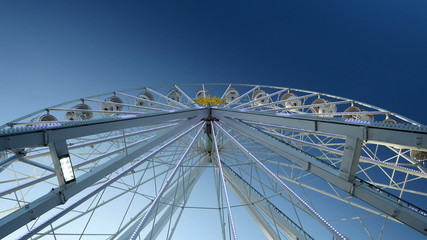 Ferris wheel with clear blue sky background.