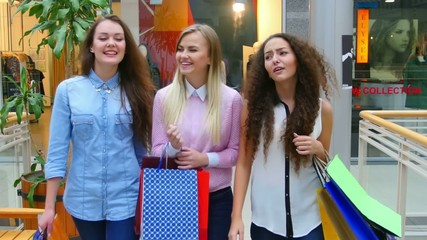 Three beautiful girls with shopping bags goes on shopping center