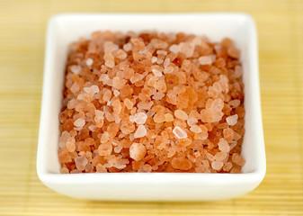 Bowl of pink himalyan rock salt against wooden background