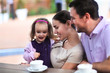 Family enjoying cup of coffee In cafe together