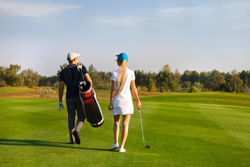 Couple playing golf on a golf course walking to the next hole