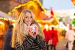 Leinwanddruck Bild - Junge Frau trinkt Glühwein auf dem Weihanchtsmarkt