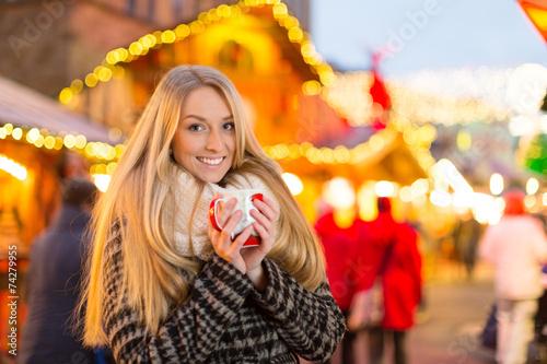 Leinwanddruck Bild Junge Frau trinkt Glühwein auf dem Weihanchtsmarkt