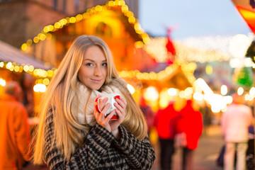 Junge Frau trinkt Glühwein auf dem Weihanchtsmarkt