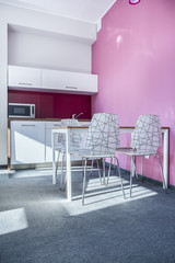 Modern kitchen with pink wall