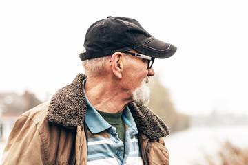 Senior man with beard wearing glasses and black cap outdoor in w