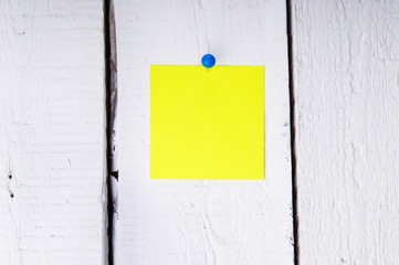 Yellow memo pad on the wooden board