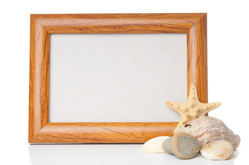 Empty wooden frame with shells on white background