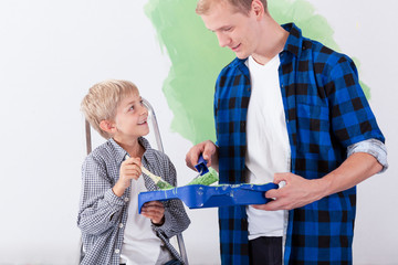 Father painting wall with son