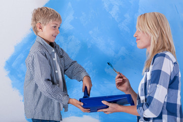Mother and son during wall painting